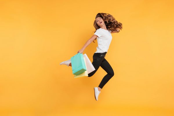 laughing-pretty-young-woman-jumping-holding-shopping-bags-1-scaled.jpg