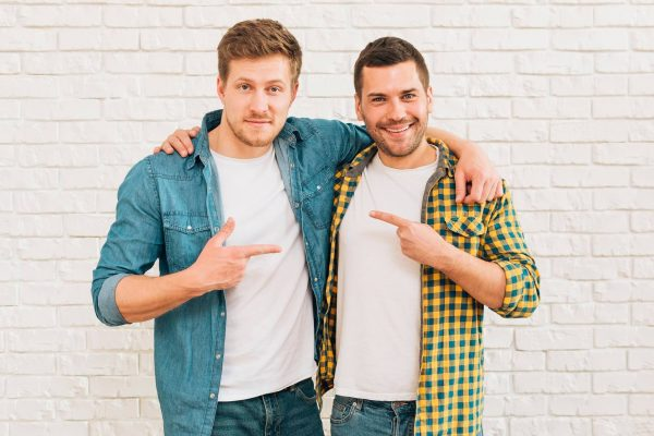 smiling-young-men-with-their-arms-around-pointing-fingers-each-other-1.jpg